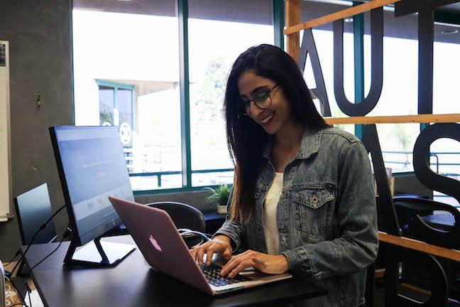 Elika smiling at laptop