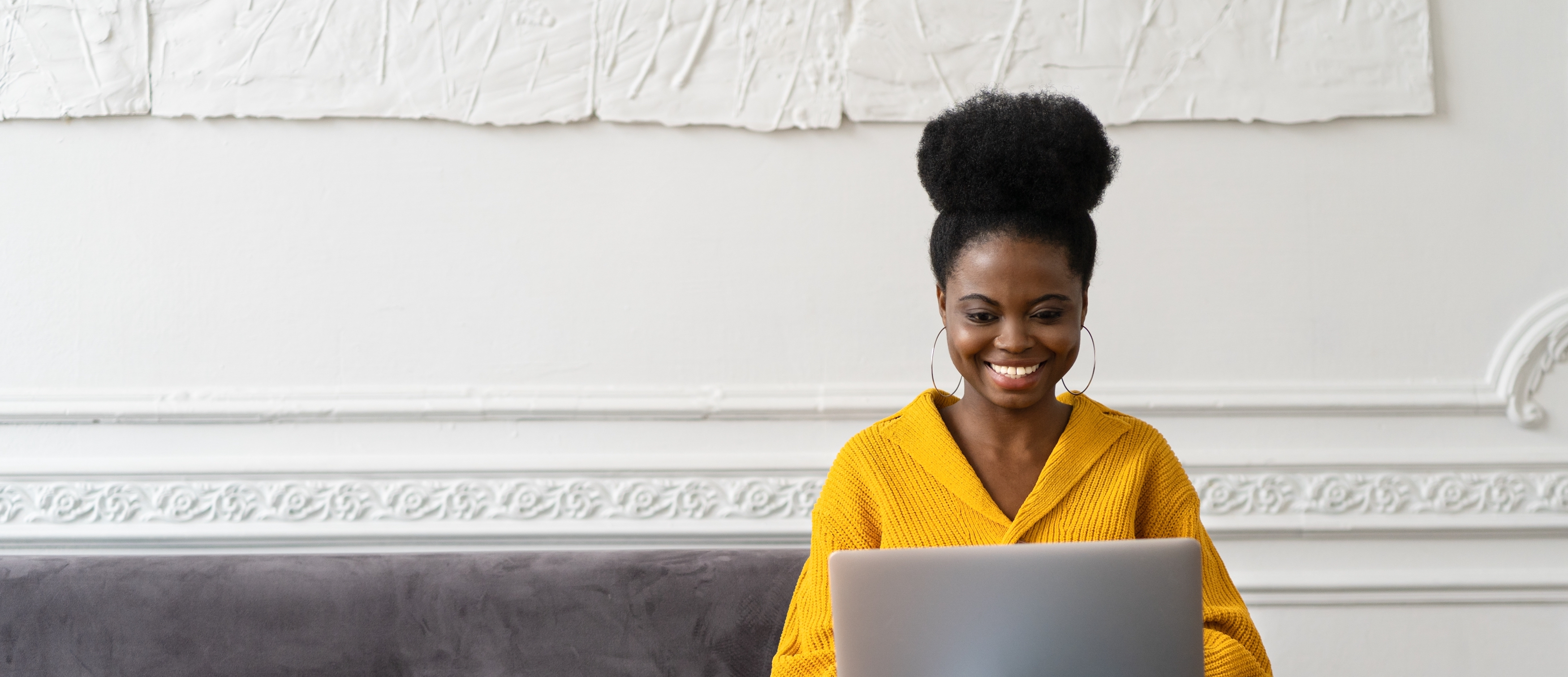 smiling-african-american-millennial-woman-with-afro-hairstyle-wear-yellow-cardigan-sitting-on-sofa_t20_LlnRLo